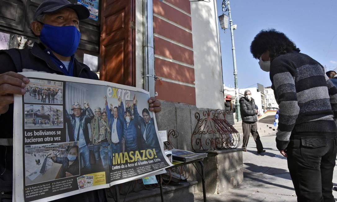 Um vendedor de uma banca de jornal em La Paz exibe um jornal.  Arce, do Movimento ao Socialismo (MAS), obteve 52,4% dos votos, ante 31,5% do ex-presidente Carlos Mesa, da centrista Comunidade Cidadã (CC) Foto: AIZAR RALDES / AFP