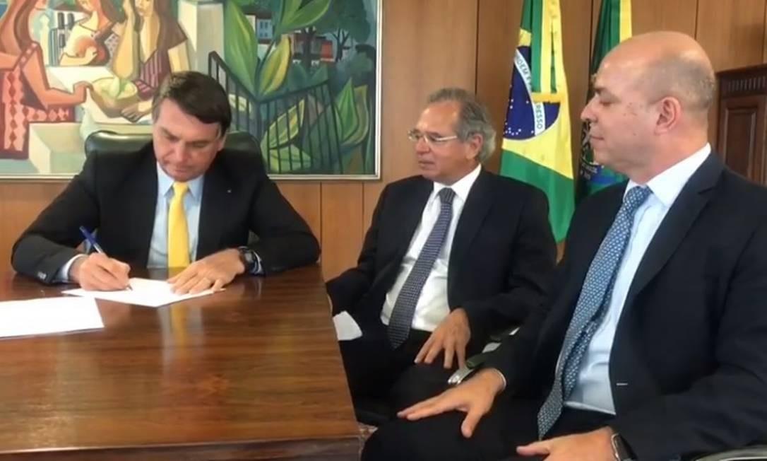 O presidente Jair Bolsonaro assina projeto de lei, ao lado do ministro Paulo Guedes e do secretário Carlos da Costa Foto: Reprodução/Facebook