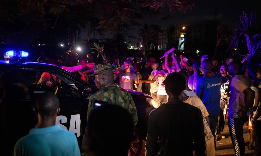 Manifestantes nigerianos cercam um carro das forças de segurança em Ikeja, no estado de Lagos Foto: Benson Ibeabuchi / AFP