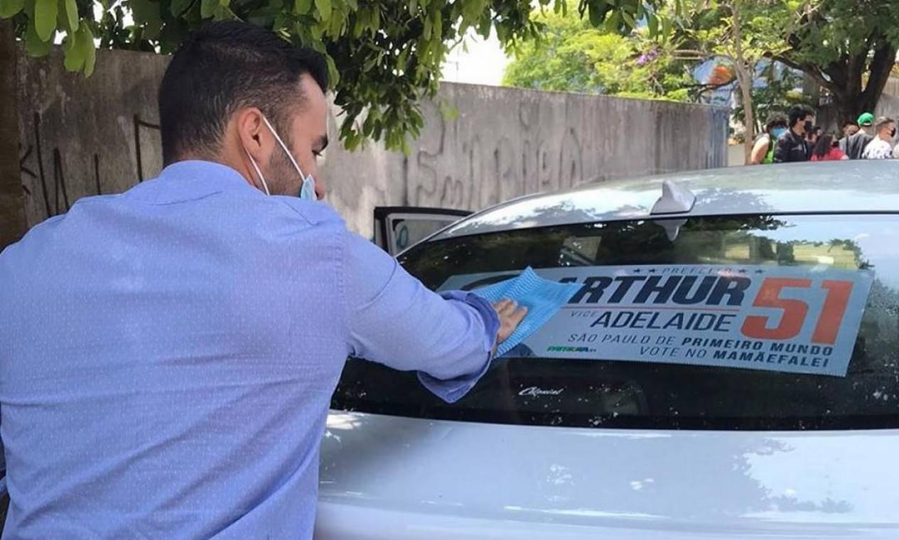 Arthur do Val aplica adesivo de campanha no vidro traseiro de carro de eleitor Foto: Reprodução / Redes Sociais - 12/10/2020