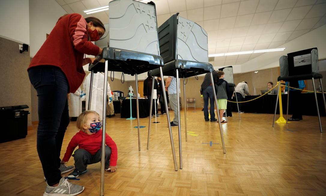 Uma eleitora marca seu voto enquanto seu filho brinca a seus pés no primeiro dia da votação antecipada em Durham, Carolina do Norte Foto: JONATHAN DRAKE / REUTERS - 15/10/2020