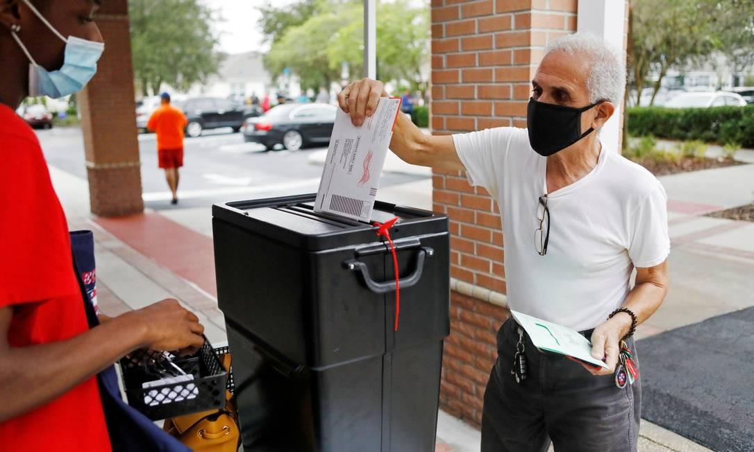 Um residente da Flórida lança sua cédula pelo correio na seção de votação da Biblioteca Winter Garden, em Orlando, Flórida. Votos antecipados são aceitos nas 50 unidades federativas dos EUA e na capital. Em apenas sete delas os eleitores precisam de uma justificativa para optar pela modalidade Foto: OCTAVIO JONES / REUTERS - 19/10/2020