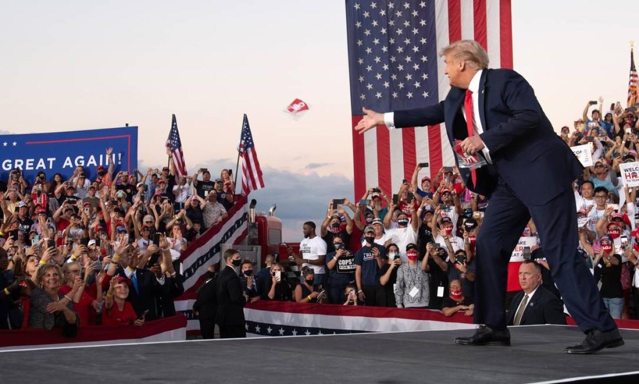 Em retomada da campanha após se curar da Covid-19, Donald Trump joga máscaras para apoiadores durante comício em Sanford, na Flórida Foto: Saul Loeb / AFP - 12/10/2020
