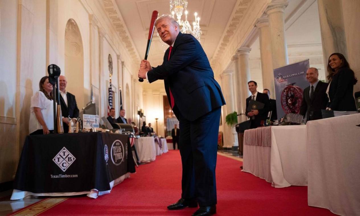 Donald Trump dá uma tacada com um bastão da Texas Timber antes de falar em um evento na Casa Branca, em Washington Foto: JIM WATSON / AFP - 02/07/2020