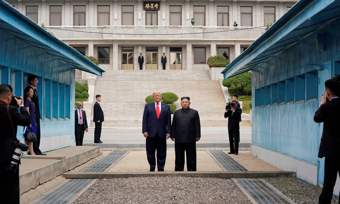 Donald Trump caminha para o lado norte da Linha de Demarcação Militar que divide as Coréias do Norte e do Sul acompanhado do líder norte-coreano, Kim Jong-un. Trump foi o primeiro presidente americano a entrar na Coreia do Norte, em junho do ano passado Foto: KEVIN LAMARQUE / Reuters - 30/06/2019