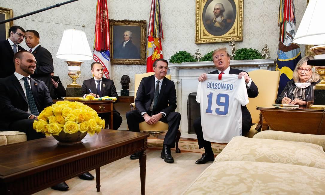 Trump entrega uma camisa personalizada, simbolizando o esporte nacional, ao presidente brasileiro, Jair Bolsonaro, durante encontro na Casa Branca, em março de 2019 Foto: Isac Nóbrega / PR - 19/03/2019