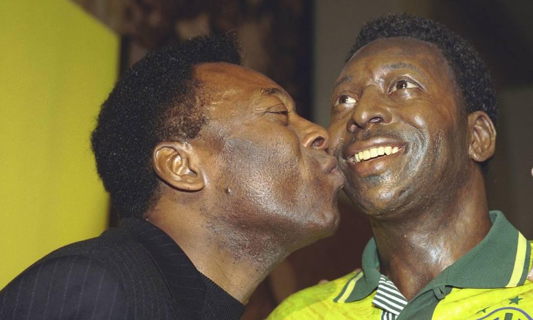Pelé beija estátua dele mesmo, em exposição sobre sua vida na Casa França-Brasil Foto: Alexandre Cassiano / Agência O Globo - 22/04/2002
