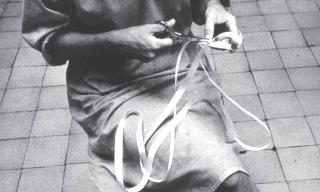 Lygia e a obra 'Caminhando' (1964), feita com tesoura e tira de papel Foto: Associação Cultural O Mundo de Lygia Clark