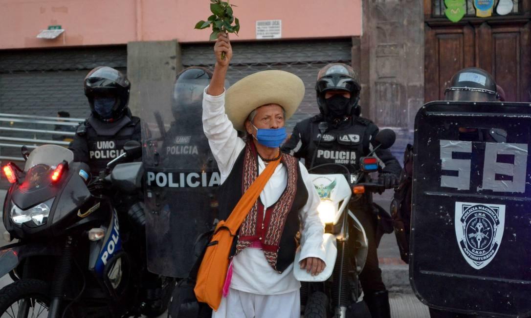 Manifestante levanta buquê de flores ao lado da tropa de choque durante protesto de trabalhares, professores e estudantes universitários contra as medidas econômicas do governo do presidente equatoriano Lenin Moreno, no centro de Quito, capital do país. Foto: RODRIGO BUENDIA / AFP