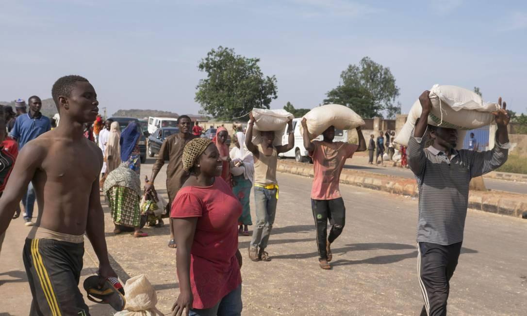 Nigerianos carregam sacos de comida na cabeça durante um saque em massa a um armazém em Jos Foto: IFIOK ETTANG / AFP/24-10-2020