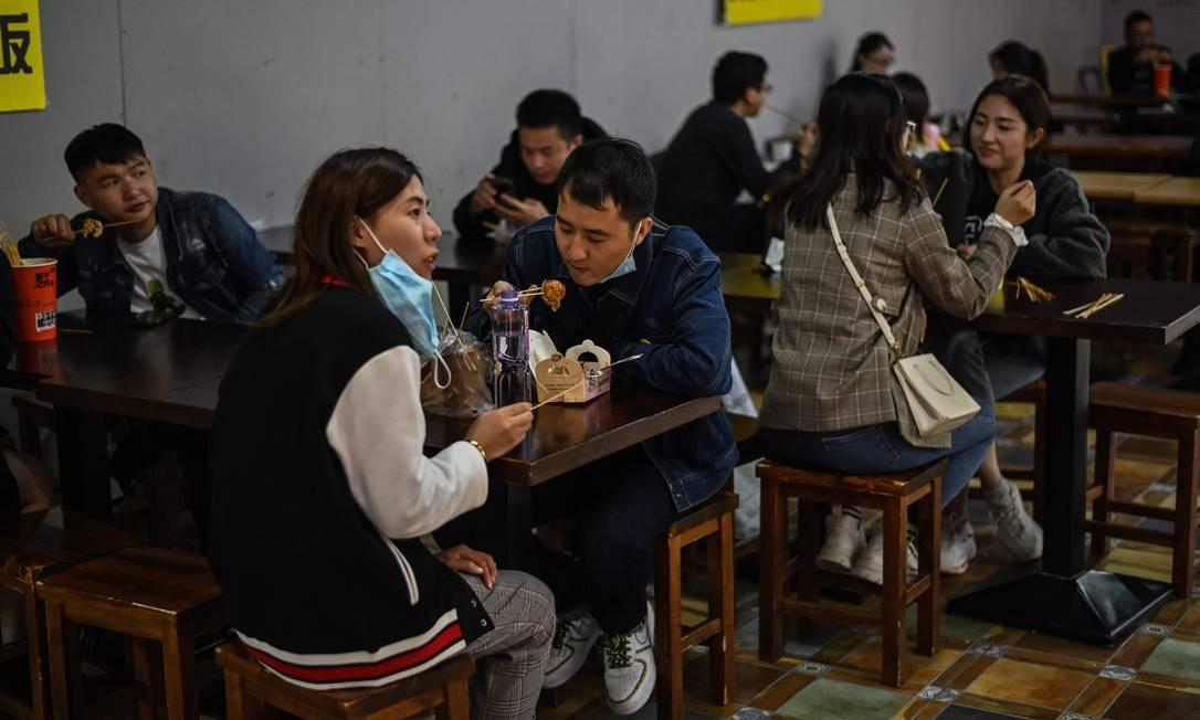 Casal usando máscara em um restaurante em Xangai no último domingo Foto: HECTOR RETAMAL / AFP