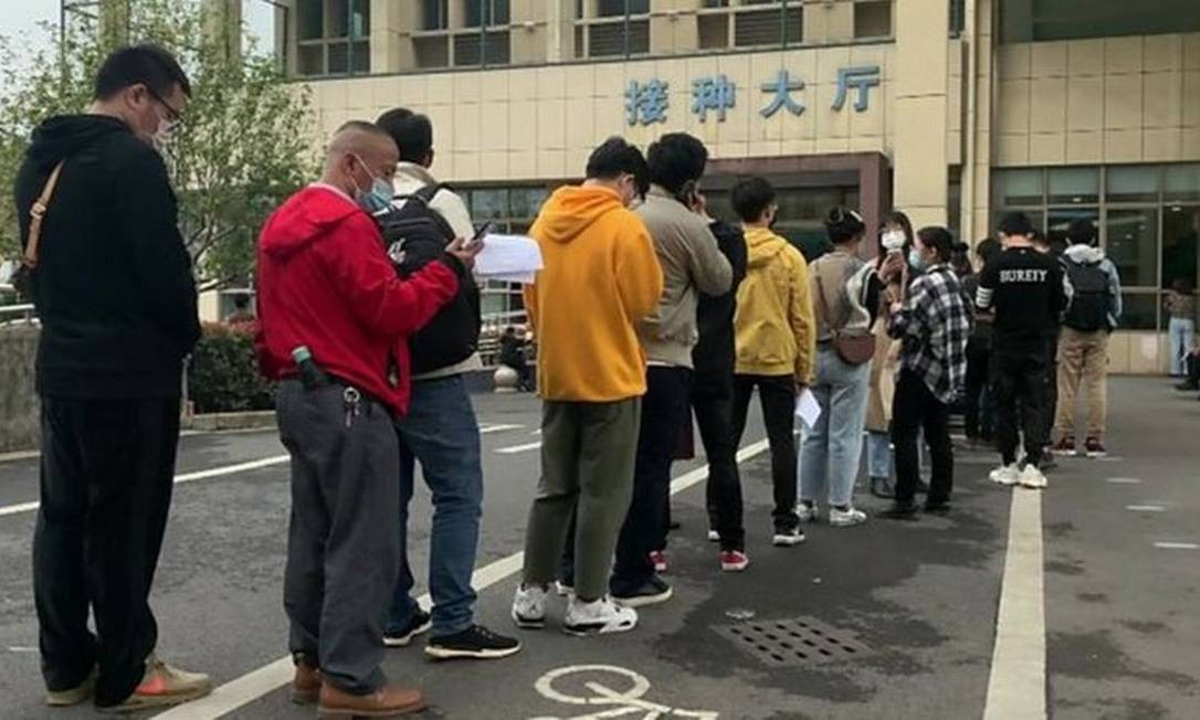 Centenas de pessoas fazem filas na cidade chinesa de Yiwu para receber vacinas em caráter emergencial Foto: -