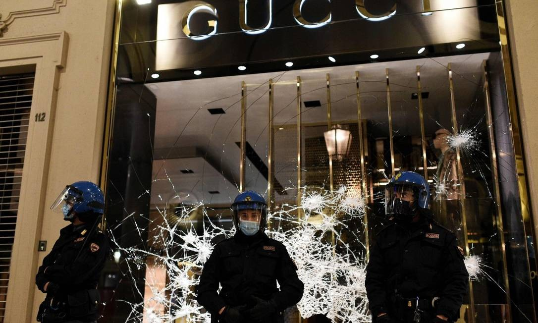 Policiais protegem loja da Gucci em Turim, destruída por manifestantes de extrema direita e torcidas organizadas Foto: MARCO BERTORELLO / AFP / 26-10-2020