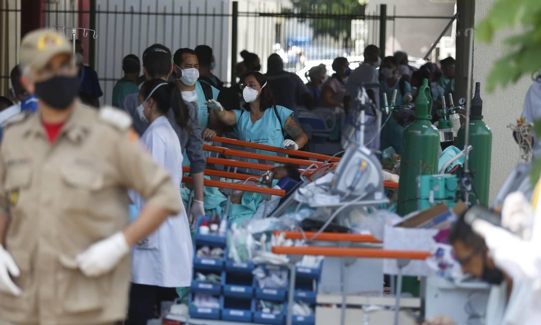 Funcionários do hospital ajudam bombeiros no resgate de pacientes Foto: Fabiano Rocha / Agência O Globo