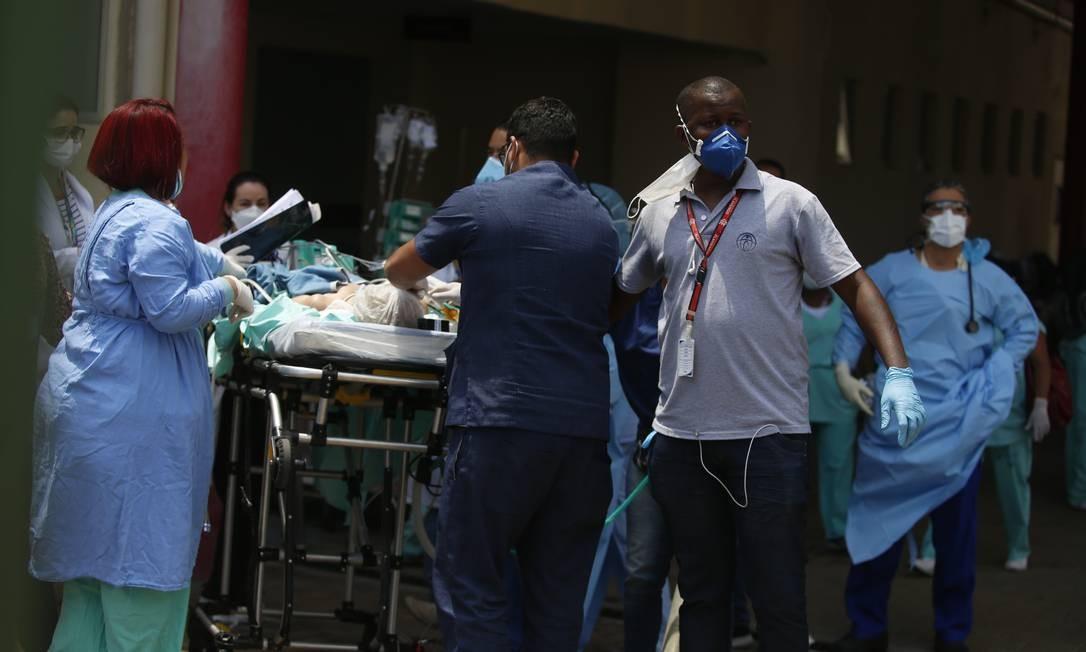 Funcionários usando equipamento de proteção individual carregam paciente na maca, para fora do hospital Foto: Fabiano Rocha / Agência O Globo