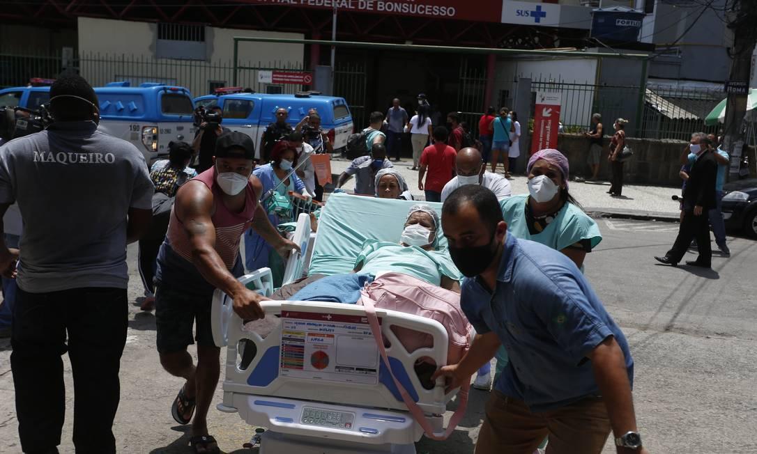Pacientes são retirado às pressas do Hospital Federal de Bonsucesso, na Zona Norte do Rio, por funcionários e voluntários Foto: Fabiano Rocha / Agência O Globo