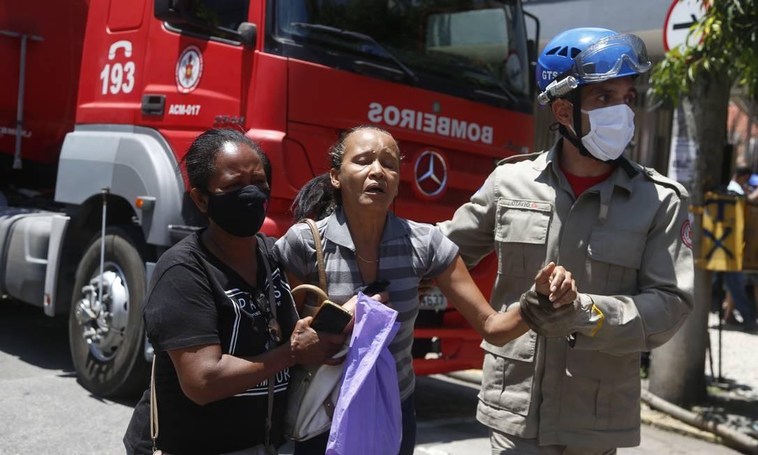 Mulher é acudida por bombeiro. Ela buscava, desesperadamente, informações sobre o sobrinho internado, e chegou a tentar invadir o hospital em chamas Foto: Fabiano Rocha / Agência O Globo
