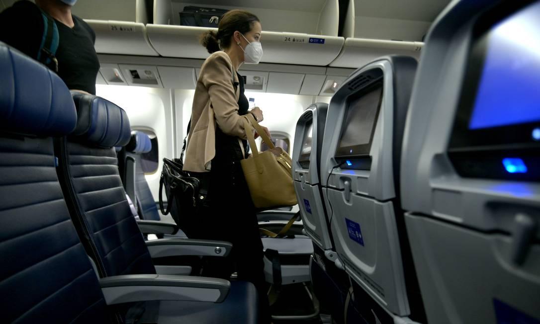 Passageira de máscara saindo da aeronave após um voo Foto: Michael loccisano / AFP