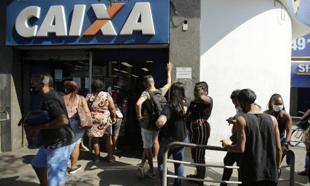 Beneficiários do auxílio emergencial fazem fila para receber o benefício em frente a uma agência da Caixa Foto: Antonio Scorza / Agência O Globo