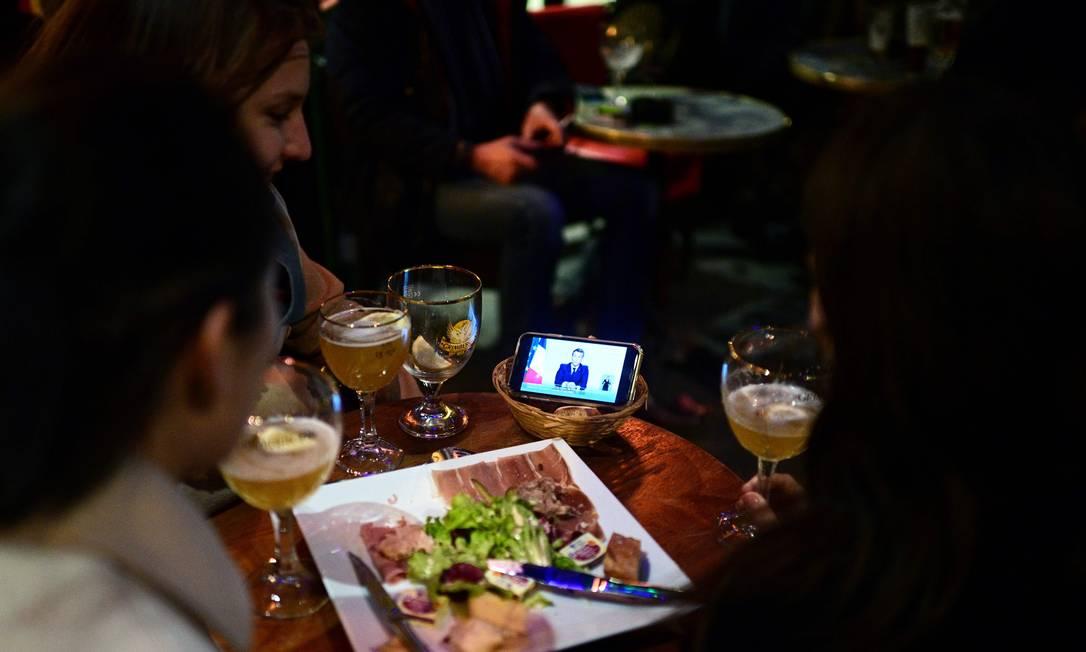 Clientes assistem ao pronunciamento do presidente Emmanuel Macron em um café em Paris. Novos casos de Covid-19 alarmaram médicos e autoridades da França. Hospitais estão em luta contra o fluxo de pacientes Foto: MARTIN BUREAU / AFP