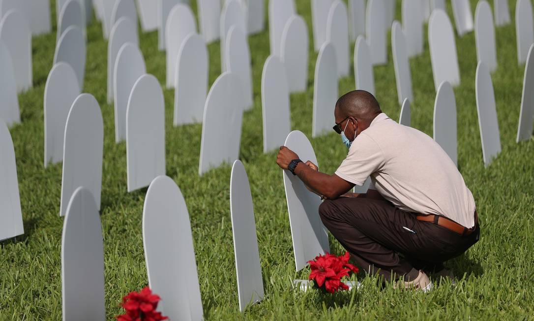 Um homem escreve o nome de um amigo perdido para Covid-19 em uma lápide durante a inauguração do memorial para as vítimas da pandemia no Griffing Par, North Miami, Flórida. Apenas na última semana, o país registrou quase 500 mil novos casos da doença Foto: JOE RAEDLE / AFP