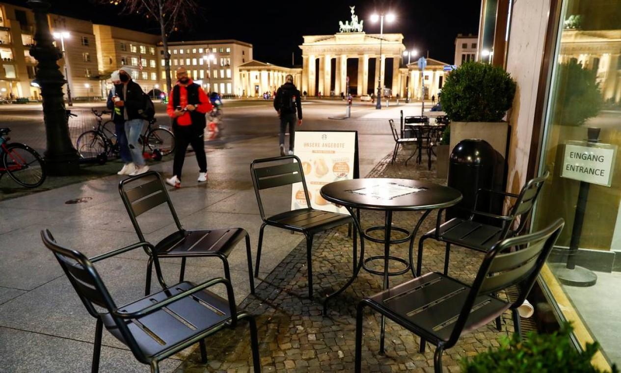 Pedestres passam por mesas vazias de um café em frente ao Portão de Brandemburgo, em Berlim, Alemanha. Governo do país decidiu nesta quarta-feira (28) decretar uma quarentena parcial a partir de 2 de novembro Foto: FABRIZIO BENSCH / REUTERS