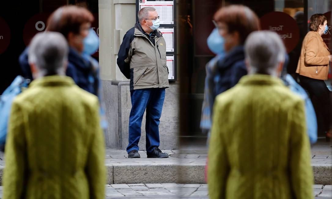 Pessoas transitam de máscara em uma rua de Berna, na Suíça. Casos, hospitalizações e mortes pela Covid-19 dobraram de uma semana para a outra ao longo de outubro no país Foto: STEFAN WERMUTH / AFP