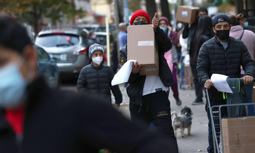 Moradores pegam caixas em centro de distribuição de comida em Nova York Foto: Michael M. Santiago / AFP