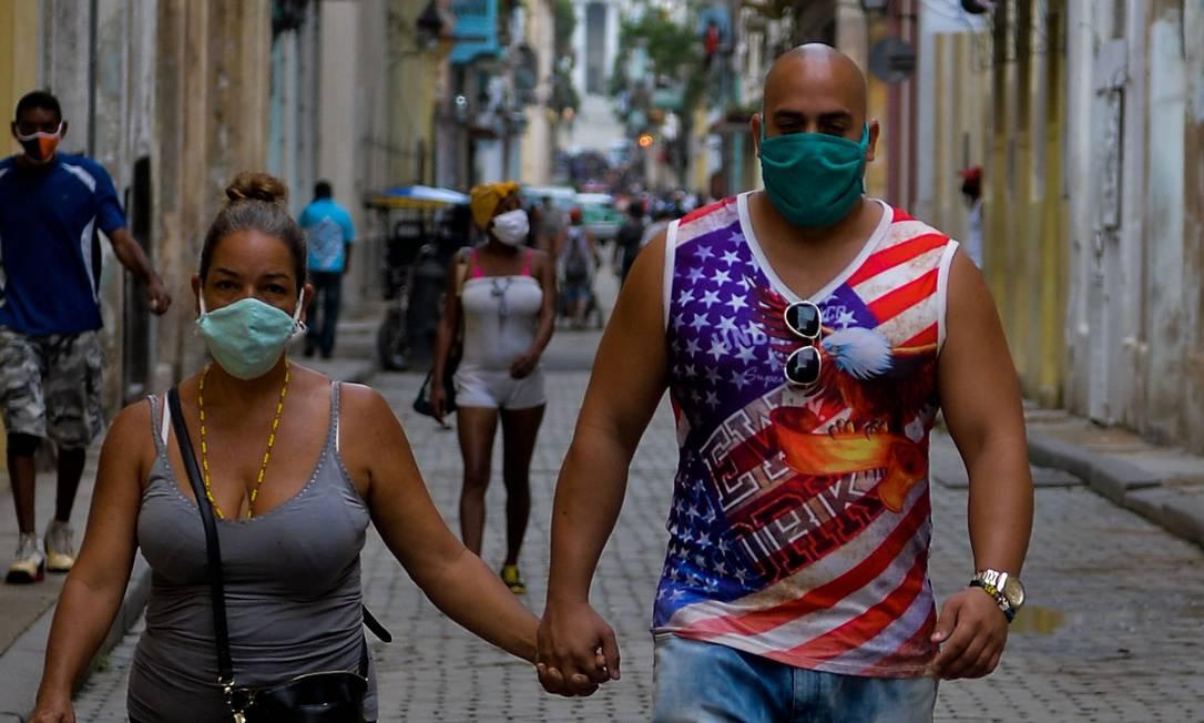 Casal com máscara passeia em Havana: cubanos vivem expectativa em relação ao resultado da eleição americana Foto: YAMIL LAGE / AFP
