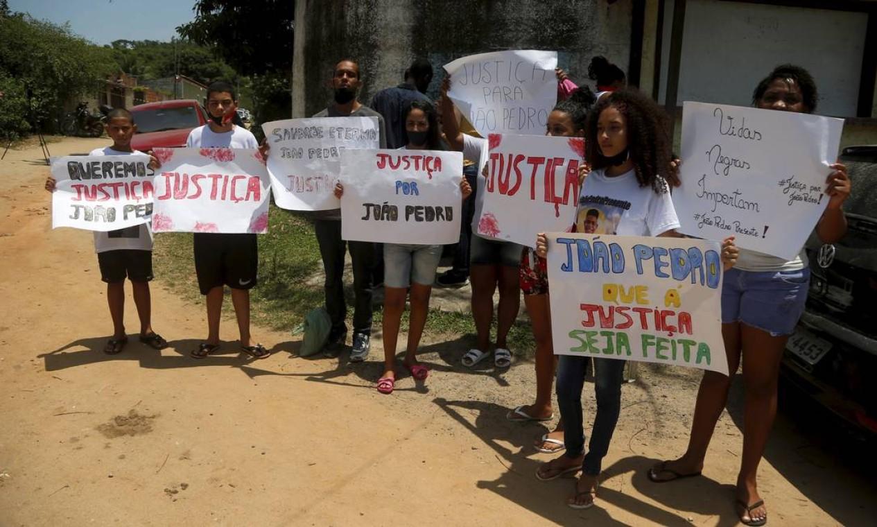 Vizinhos e amigos de João Pedro, com cartazes, pedem Justiça Foto: FABIANO ROCHA / Agência O Globo
