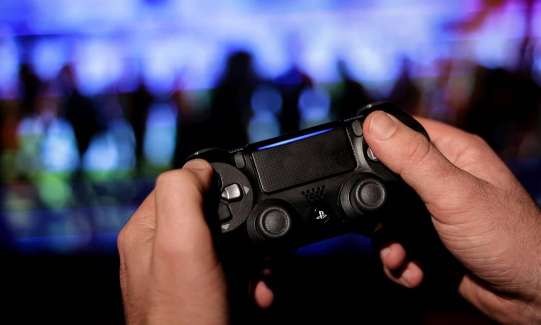 Um jogador usa controle de PS4 Foto: KENZO TRIBOUILLARD / AFP