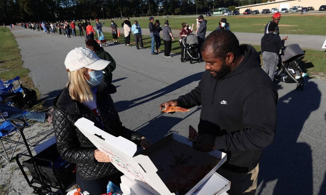 Voluntária distribui pizzas para eleitores que aguardam para votar de modo antecipado em Lawrenceville, na Geórgia; estudos mostram que filas são mais longas em bairros negros e pobres Foto: JUSTIN SULLIVAN / AFP / 30-10-2020