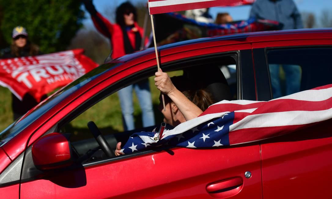Mulher com bandeira americana passa por apoiadores de Donald Trump na Pensilvânia, estado decisivo para o resultado das eleições de 3 de novembro Foto: Mark Makela / AFP