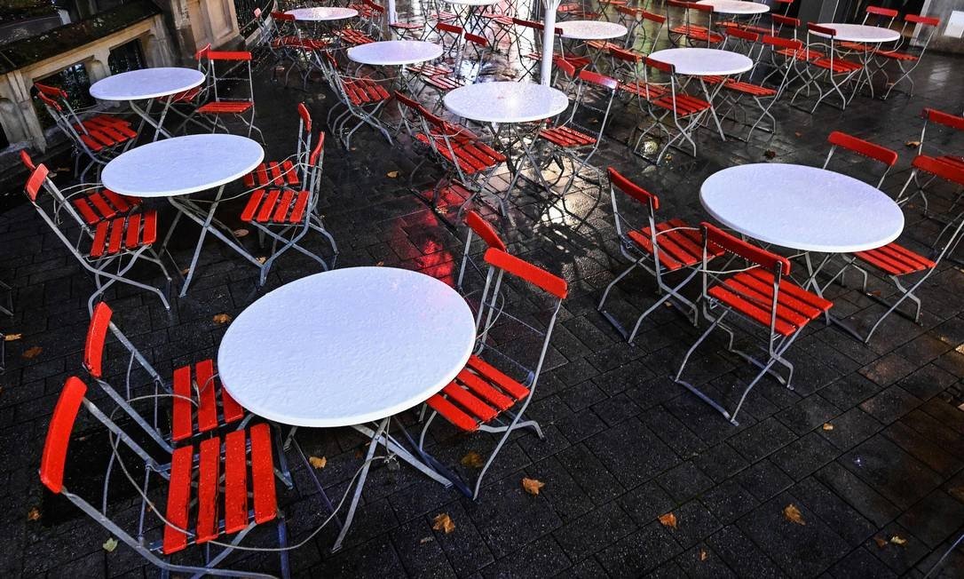 Mesas e cadeiras estão trancadas do lado de fora de um restaurante fechado na cidade velha de Colônia, na Alemanha Foto: INA FASSBENDER / AFP