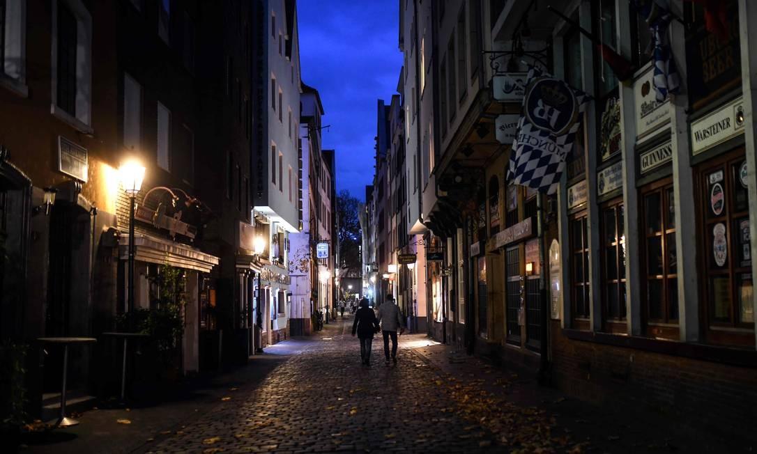 As pessoas passam por bares e restaurantes fechados na cidade velha de Colônia, Alemanha Foto: INA FASSBENDER / AFP