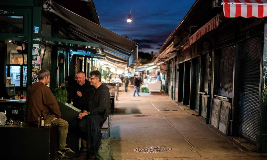 Clientes se sentam em um bar próximo a barracas de mercado fechadas no Naschmarkt, em Viena, algumas horas antes de um segundo bloqueio durante a nova pandemia do coronavírus. O governo da Áustria anunciou no sábado uma segunda paralisação em massa e um toque de recolher até o final de novembro, em uma tentativa de conter os números crescentes de infecção por coronavírus Foto: GEORG HOCHMUTH / AFP