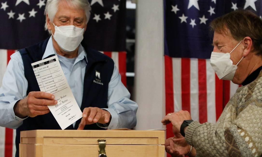 Homem lança sua cédula em uma urna pouco depois da meia-noite, quando foi aberta a votação para a eleição presidencial dos EUA no vilarejo de Dixville Notch, New Hampshire, EUA Foto: ASHLEY L. CONTI / REUTERS