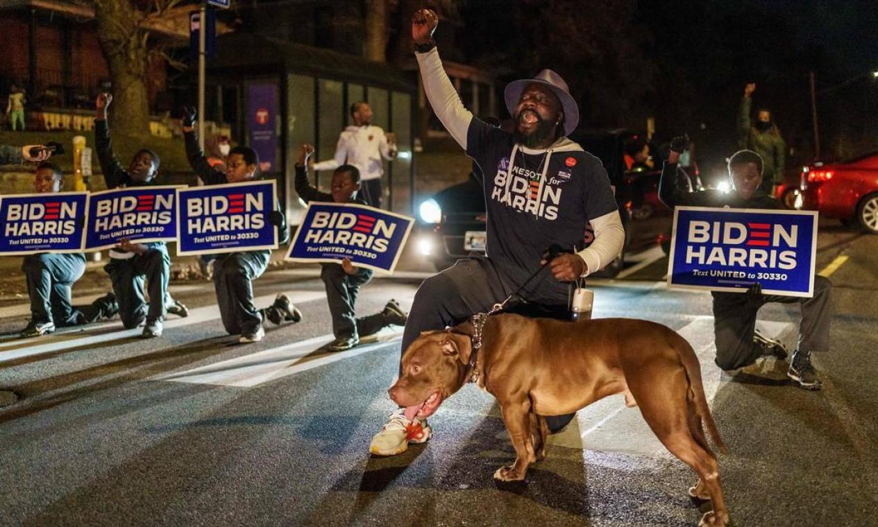 Eleitores que apoiam o candidato Joe Biden se ajoelham e bloqueiam a estrada perto de um local de votação em Minneapolis Foto: KEREM YUCEL / AFP
