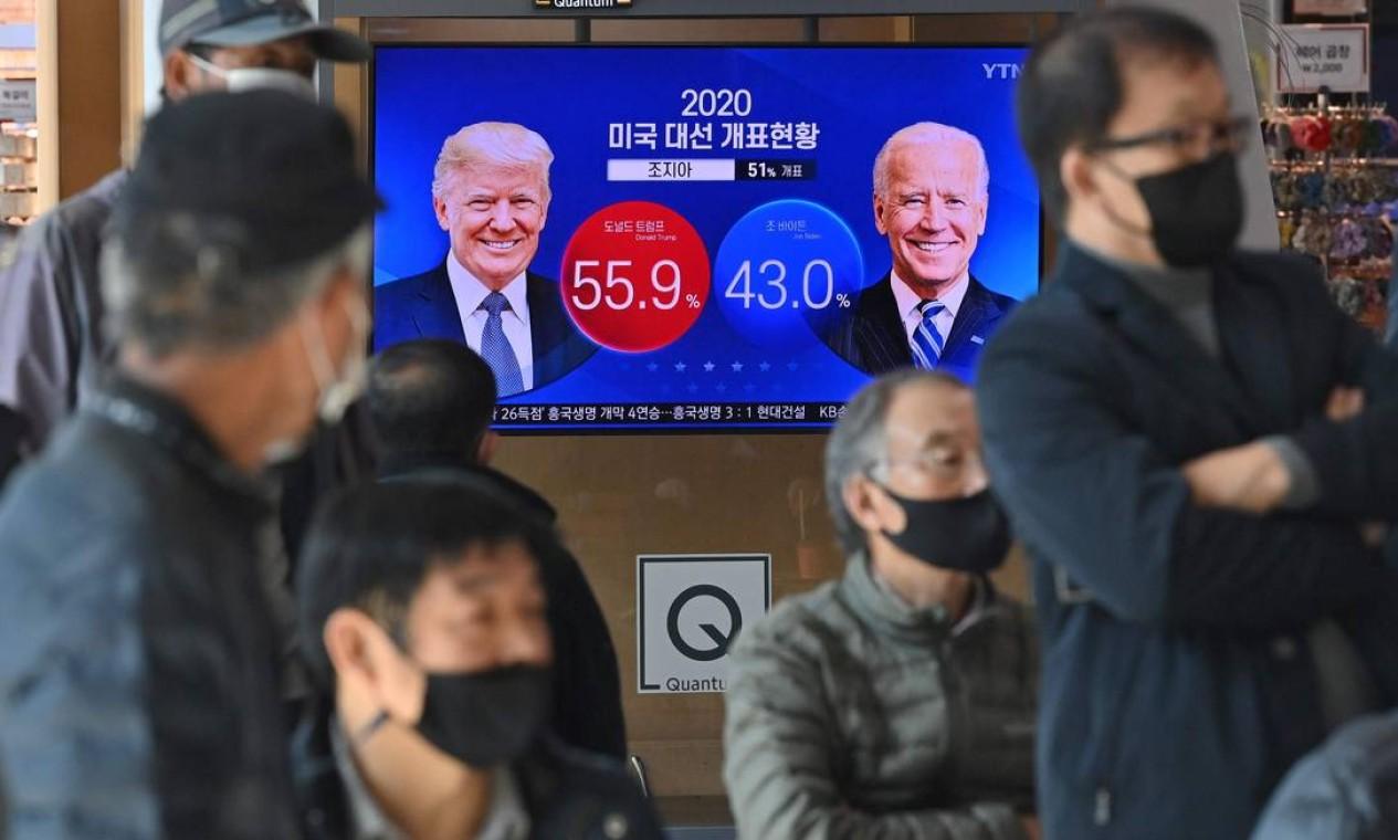 Eleitores acompanham a resultados das eleições em uma estação ferroviária em Seul Foto: JUNG YEON-JE / AFP