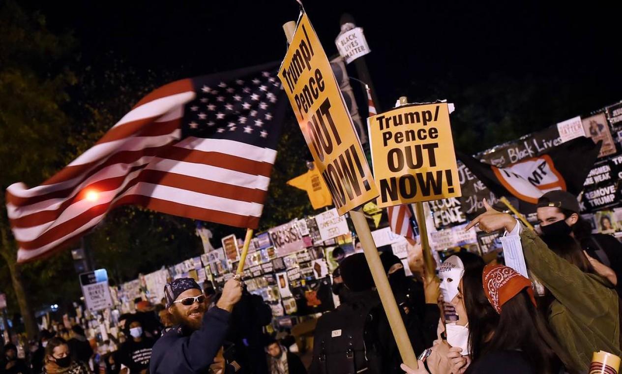 Apoiadores de Trump acenam com uma bandeira dos EUA diante de manifestantes na praça Black Lives Matter em frente à Casa Branca em Washington Foto: OLIVIER DOULIERY / AFP
