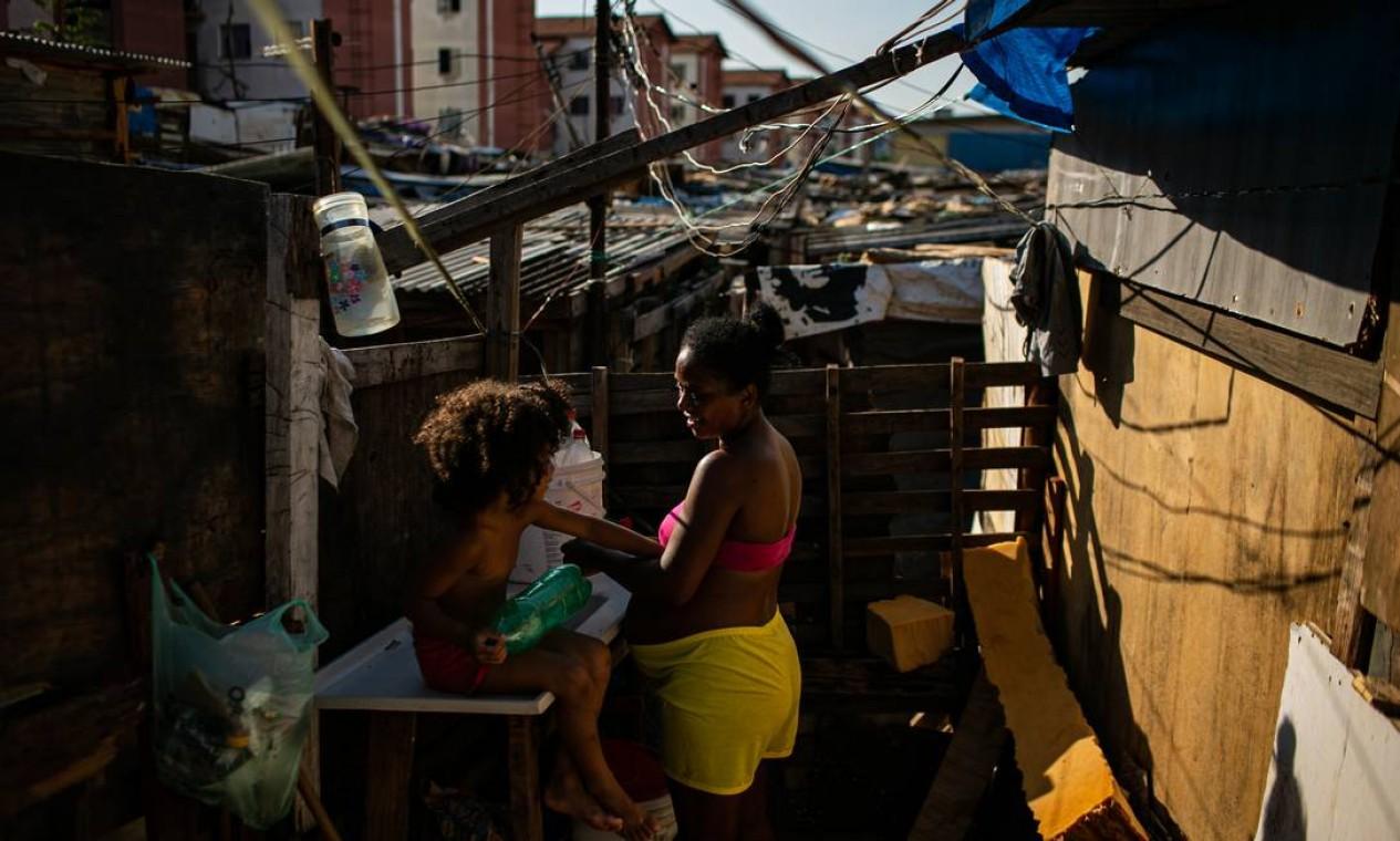 Grávida de seis meses, Gizelia Sebastiana, de 39 anos, cuida de uma das filhas do lado de fora barraco de madeira em que vive: lugar tem 222 famílias que já ouviram reiteradas promessas de moradia Foto: Hermes de Paula / Agência O Globo