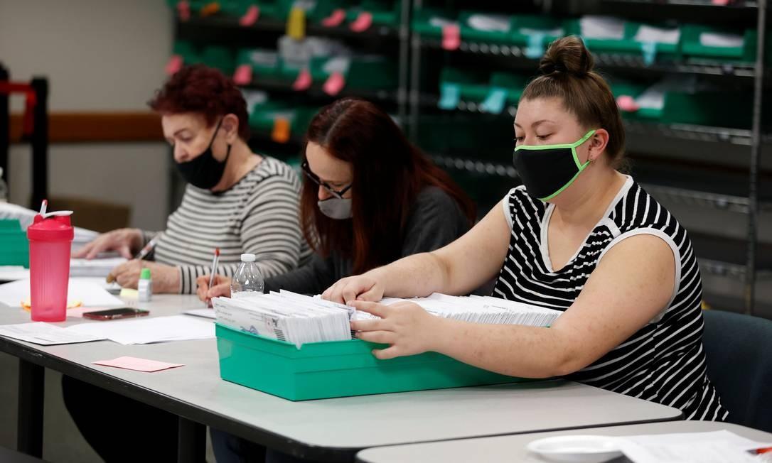 Trabalhadore eleitorais contam cédulas enviadas pelo correio, em Lehigh County, Pensilvânia. Michigan e Wisconsin também fazem parte dos chamados estados-chave Foto: RACHEL WISNIEWSKI / REUTERS