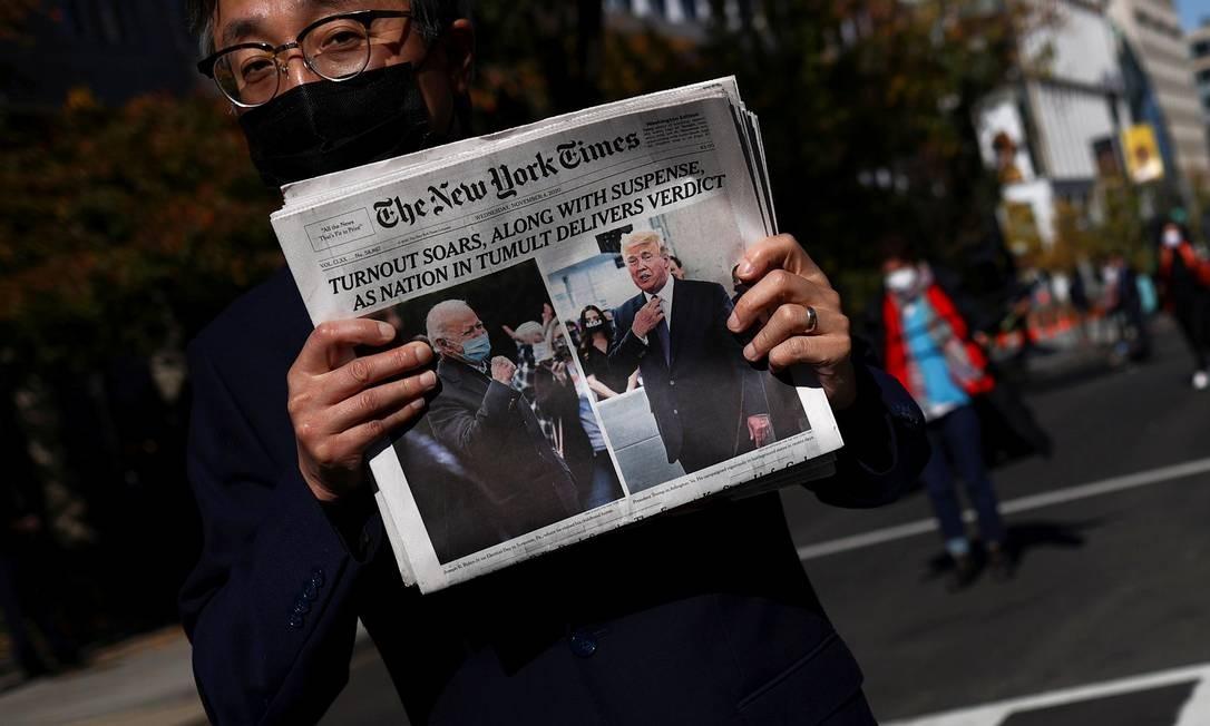 Um homem segura a edição do dia do jornal The New York Times, perto da Casa Branca, após o dia da eleição, em Washington Foto: HANNAH MCKAY / REUTERS