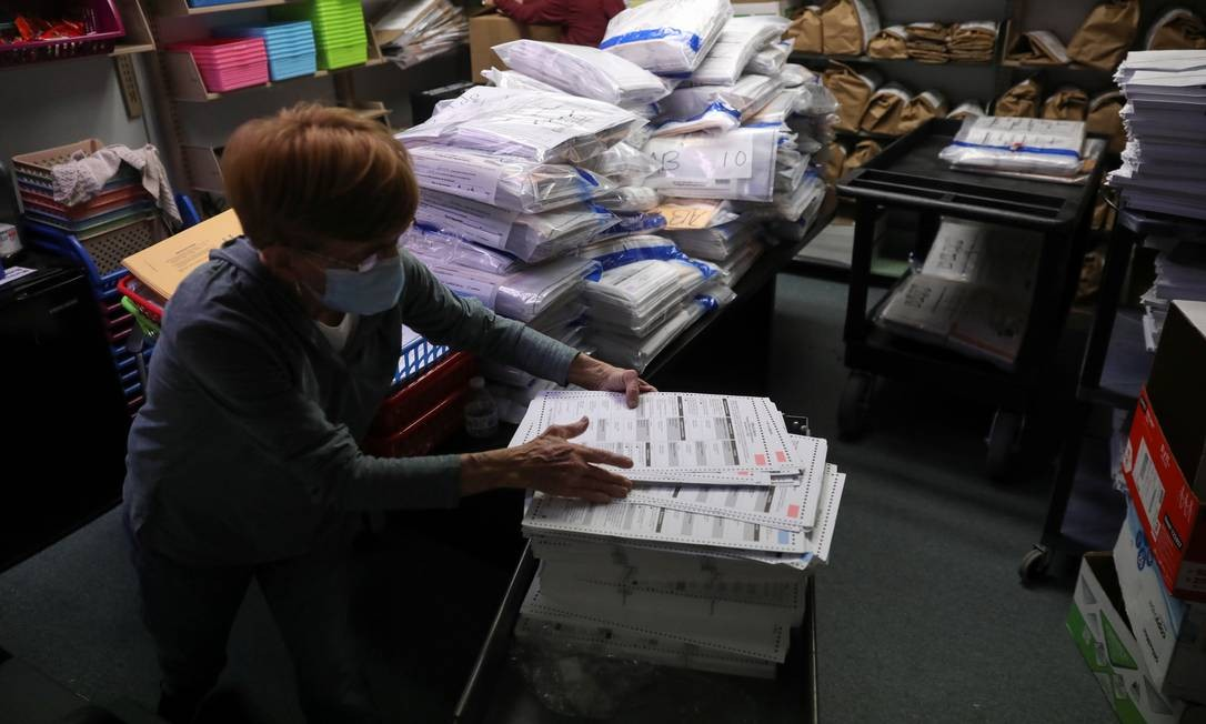 Uma oficial eleitoral trabalha na sala de votação organizando cédulas não utilizadas devolvidas da zona eleitoral após o dia da eleição em Kenosha, Wisconsin Foto: DANIEL ACKER / REUTERS