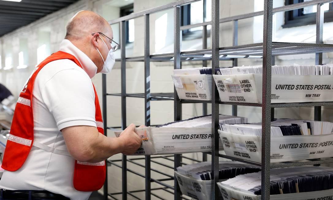 Funcionário do condado de Chester, na Pensilvânia, leva cédulas enviadas por correio para contagem Foto: RACHEL WISNIEWSKI / REUTERS