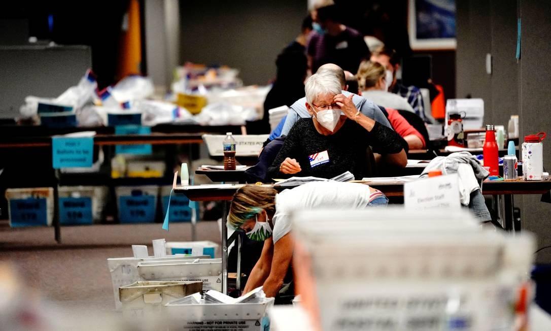 Um funcionário da pesquisa processa cédulas na noite do dia da eleição em Milwaukee, Wisconsin Foto: Bing Guan / REUTERS