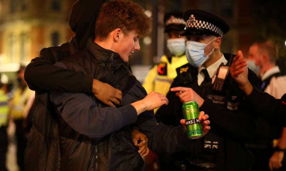 Policial orienta jovens a deixarem rua do bairro de Soho, em Londres, a poucas horas do início do lockdown na capital britânica nesta quarta-feira (4) Foto: HENRY NICHOLLS / REUTERS