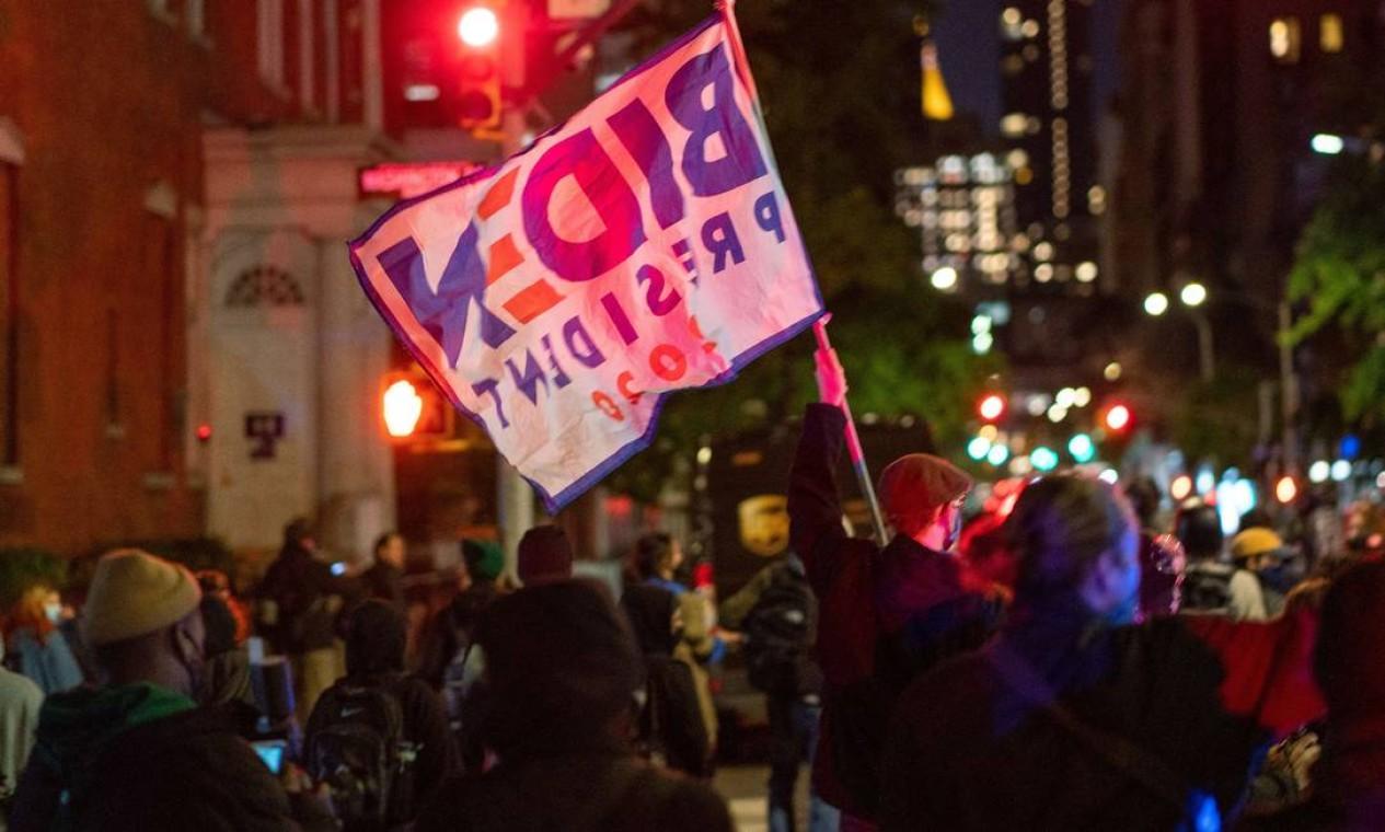Manifestante agita bandeira do candidato democrata Joe Biden, na cidade de Nova York. Foto: David Dee Delgado / AFP