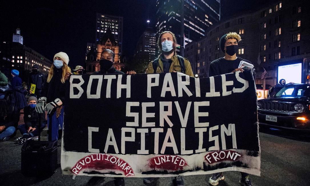"""""""Ambos partidos servem ao capitalismo"""", diz o cartaz de manifestantes na Copley Square, diante da Biblioteca Pública de Boston, Massachusetts Foto: JOSEPH PREZIOSO / AFP"""