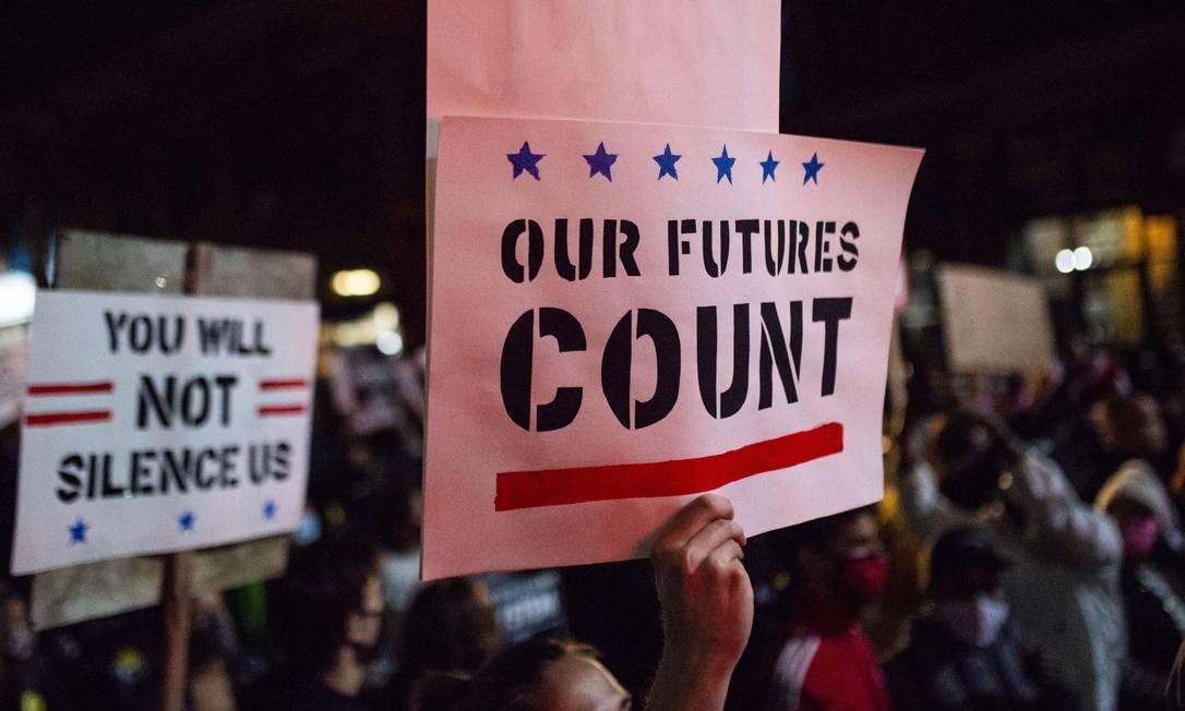 """""""Nosso futuro importa"""" e """"Vocês não vão nos calar"""", dizem cartazes vistos na marcha na Cedar Avenue em Minneapolis, Minnesota, contra as tentativas do presidente Donald Trump de impedir a contagem das cédulas Foto: Stephen Maturen / AFP"""